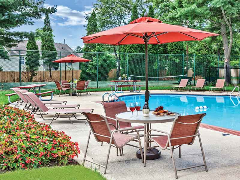 Outdoor swimming pool and tennis courts at Cedar Brook Apartment Complex