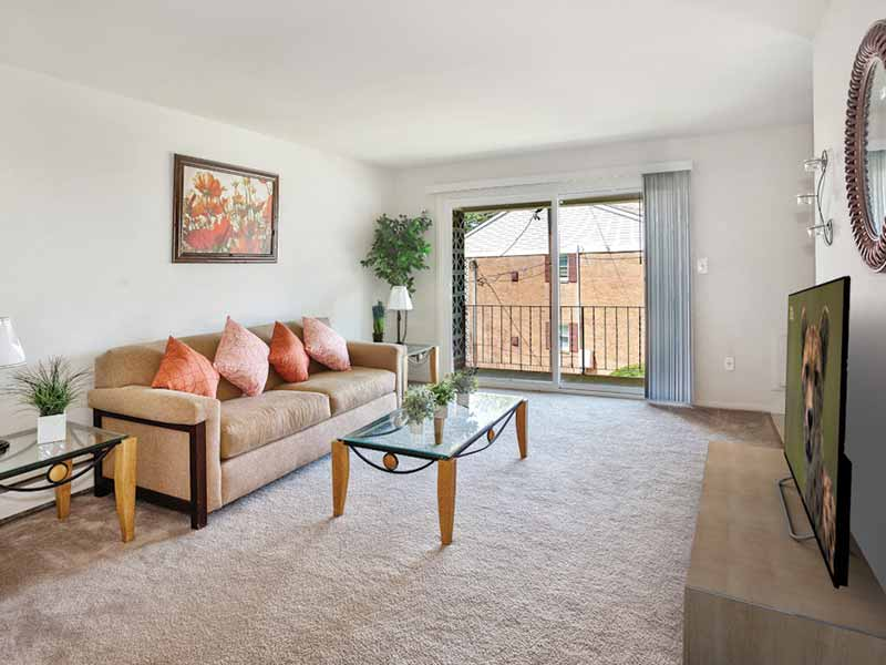 Spacious apartment living room with sliding glass doors to a balcony at Orchard Park