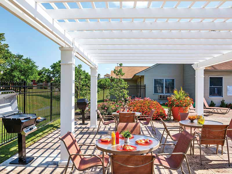 Barbeque and picnic area shaded by a pergola at Stonebridge Apartments
